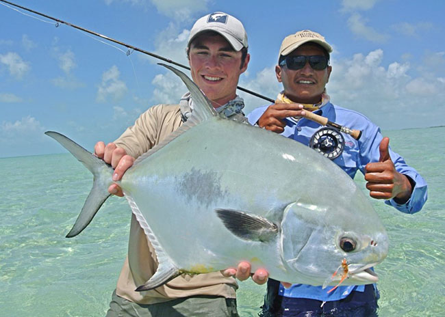 Zachary and his tour guide showing their catch over the shallow waters of the island.