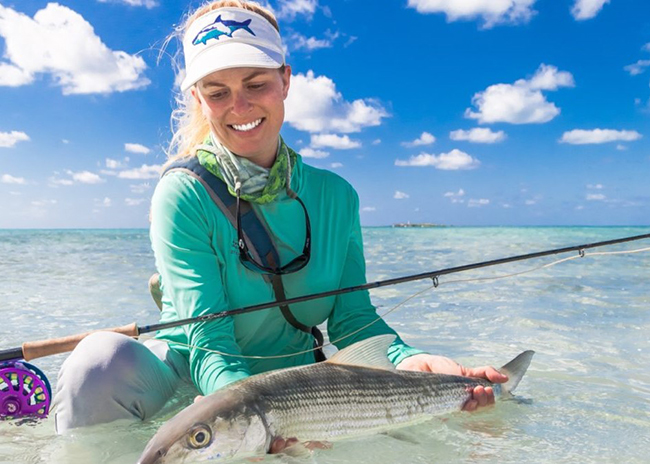 Judy holding a fish she caught during her first fly fishing day in Cozumel.